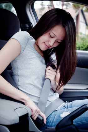 young girl driver buckling seat belt