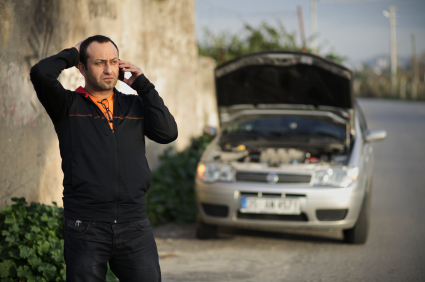 man with phone and broken car